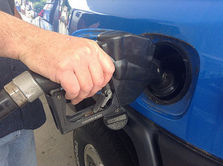 A hand and gas pump filling a gas tank