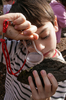 A boy looking at a rock through a magnifying glass