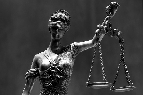 A sculpture of blind justice holding a balance