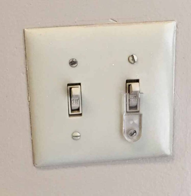 A light switch lock mounted on a toggle switch